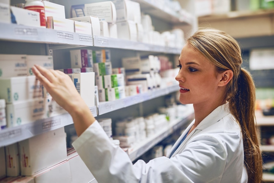 Pharmacist overlooking stock on a shelf
